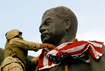 U.S. Marine covers the face of a statue of Iraqi President Saddam Hussein Baghdad 2003