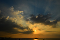 Sunset over the gulf of Beirut with rays piercing the clouds photo by vartkesn