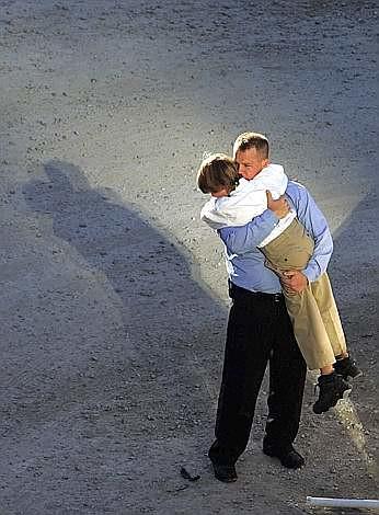 Un uomo abbraccia suo figlio sul fondo di Ground Zero (Reuters)