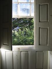 """""""Via-o sentado nos poiais azuis da sala, um pouco encostado à pequena portada da janela que tinha um postigo talhado ao centro;"""""""