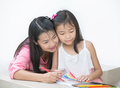 Mon and girl drawing a home work photo by anekphoto