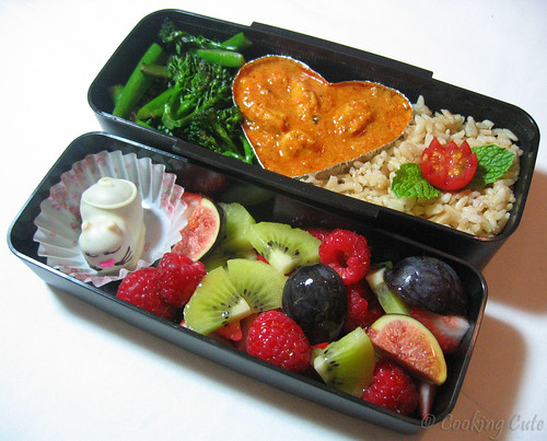 [one bento tier with Indian butter chicken, aromatic brown jasmine rice, and broccolini; second bento tier with chocolate kitten and fresh fruit]