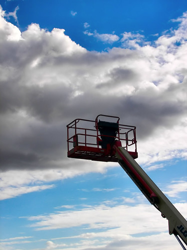 Holding Up The Clouds - a manlift with a cloudy backdrop in Stayton Oregon