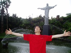 Dooshik spreading out his arm in front of Jesus statue
