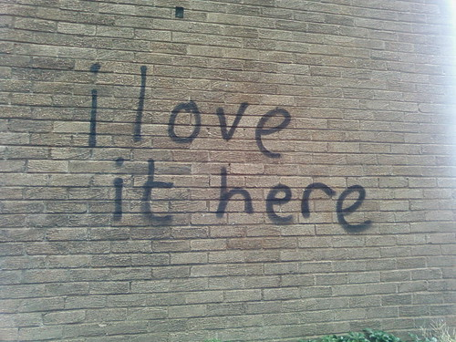 IMAGE: I LOVE IT HERE spray-painted across one of the University buildings.