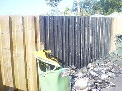 Melted recycling bin next to blackened fence