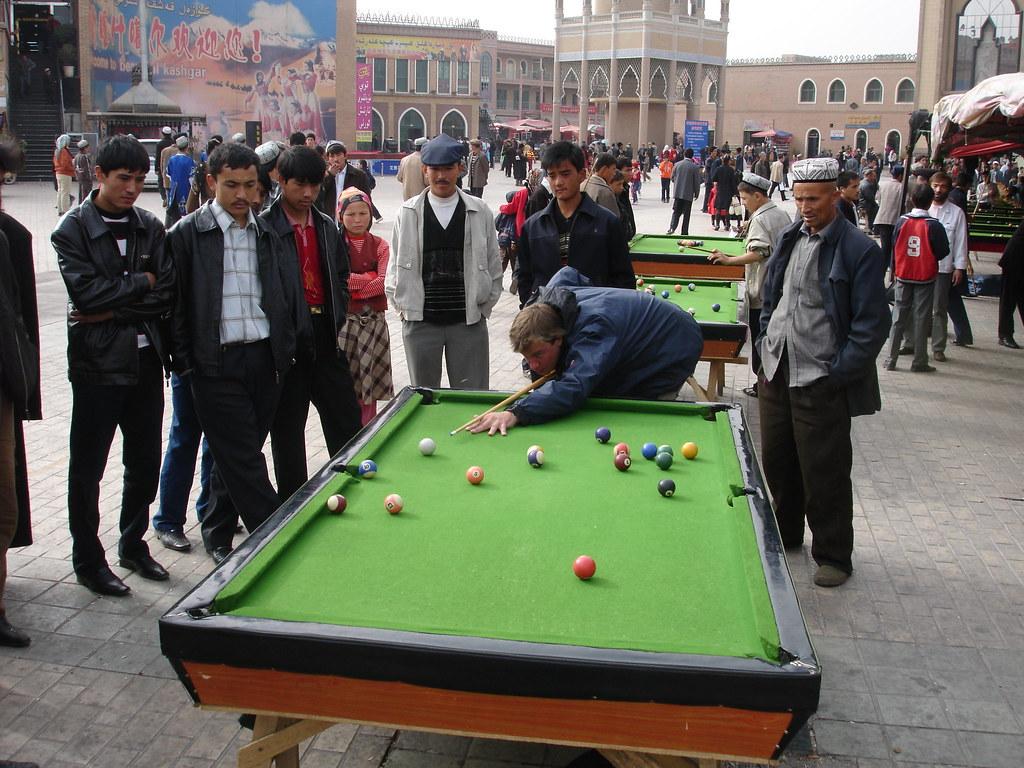 Tom playing snooker with an audience in Kashgar