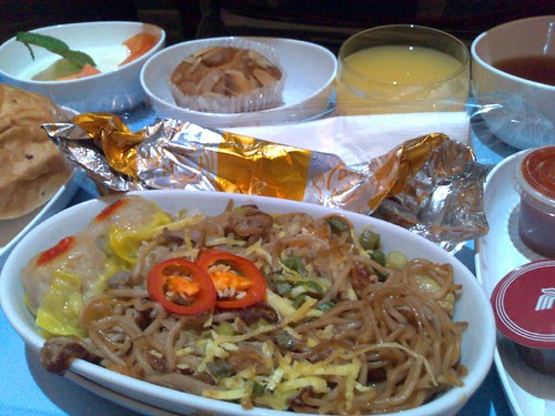 Stir-fried noodles with roast duck and vegetables served with steamed pork siew mai
