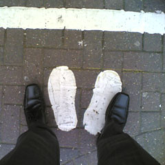 Two footsteps painted on the ground by a cash machine