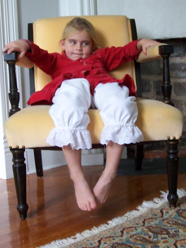 little girl.  big chair.  pantaloons.