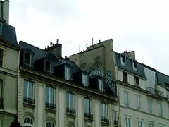 不知是怎麼爬上人家屋頂亂畫的?